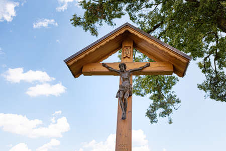 Corridor cross with Jesus in front of blue cloudz sky and branches - Calvary Editorial