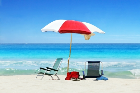 red straw: Parasol and two beach chairs on tropical beach on sunny day