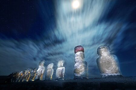 Easter Island statues at night with moonlight and stars in the backgorund photo