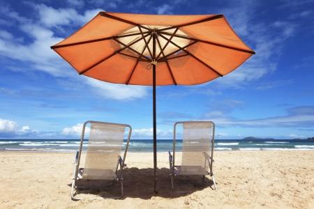 White beach chairs and orange parasol on a tropical beach