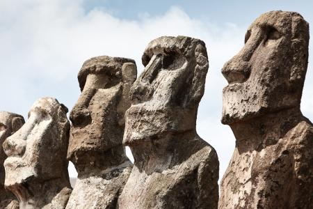 moai: Caras de cuatro moai piedra en isla de Pascua en día soleado