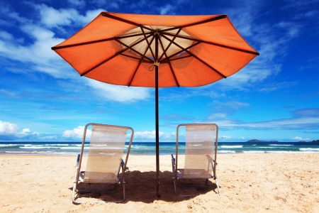 folding chair: White beach chairs and orange parasol Stock Photo