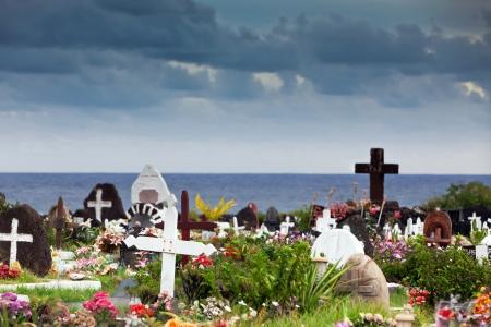 memorial cross: Memorial piedras y flores de colores en un cementerio en Hanga Roa, Isla de Pascua, bajo el cielo tormentoso Editorial