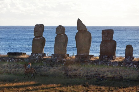 Five standing moai on seashore and a girl riding a horse photo