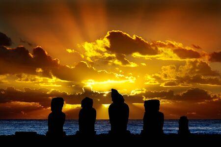 moai: Siluetas de pie contra moai dramático ocaso naranja Foto de archivo