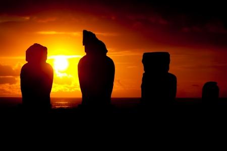 moai: Cuatro moai contra dramático ocaso rojo y naranja en Isla de Pascua Foto de archivo