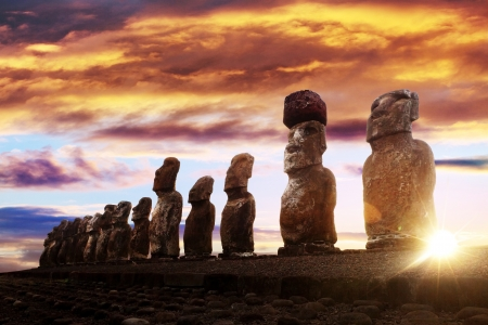 moai: Standing moai in Easter Island against rising sun and orange sky Stock Photo