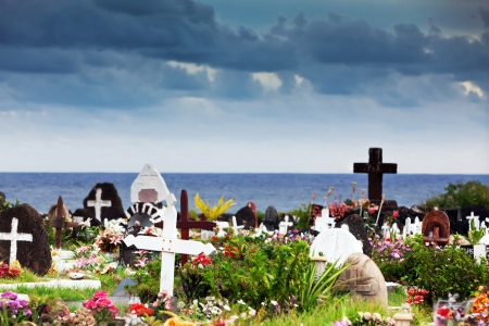 Memorial stones and colourful flowers in a graveyard in Hanga Roa, Easter Island, under thundery sky