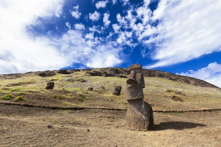moai: Moais Parcialmente enterrado en las laderas y las nubes suaves en el cielo bule brillante en Isla de Pascua