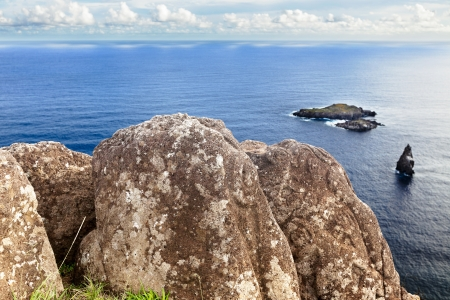 rapa: Massive rock with carvings against open sea in Easter Island