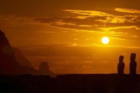 moai: Dos siluetas moai en la salida del sol de oro en Isla de Pascua