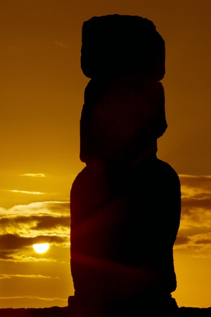Silhouette of a standing moai against orange sunrise in Easter Island photo
