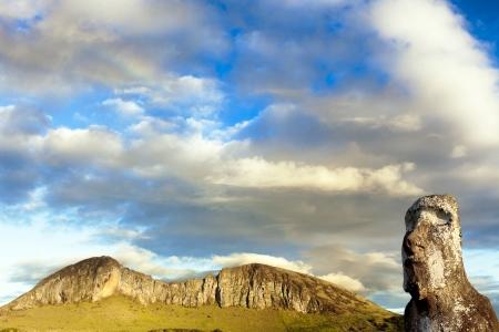 rano raraku: Head of moai with mountain and a small rainbow  in background