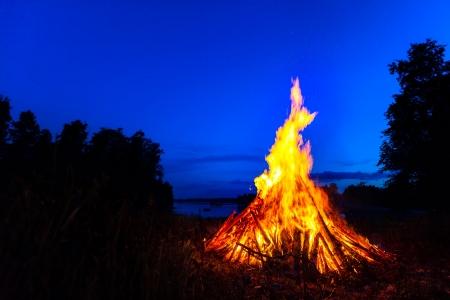 Groot vreugdevuur tegen blauwe nachtelijke hemel