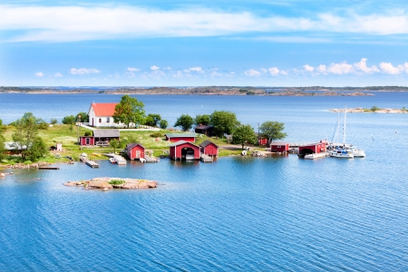 Small village with red buildings in Finnish archipelago on a sunny day