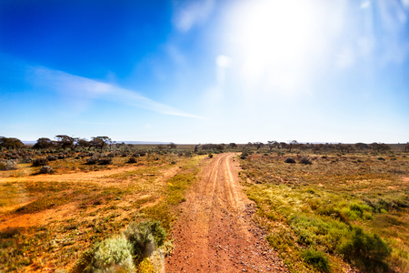 Small gravel road in Australian outback in bright sunshine photo