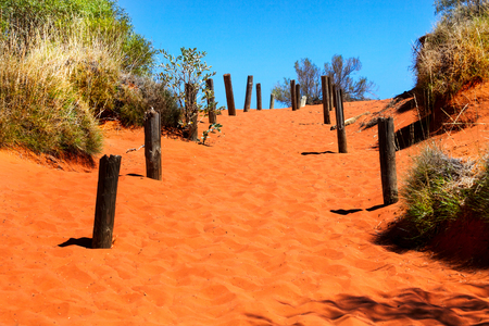 Bright orange sandy path in Australian outback and blue sky