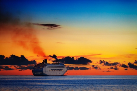 Large cruise ship on calm sea at orange sunset photo