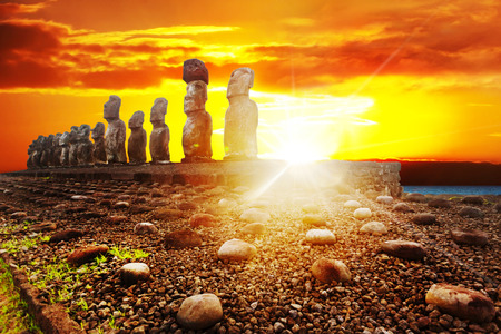 Fifteen standing moai in Easter Island in dramatic orange sunset