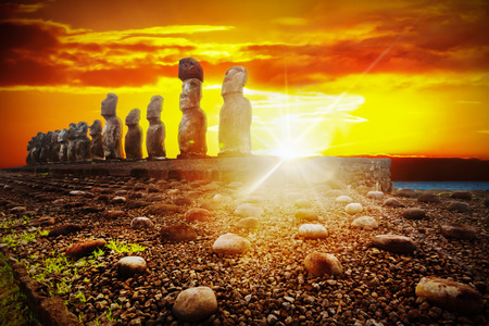 Standing moais against dramatic orange and golden sunset in Easter Island, Chile 版權商用圖片