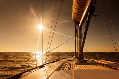 Sailing towards golden sunset at open sea