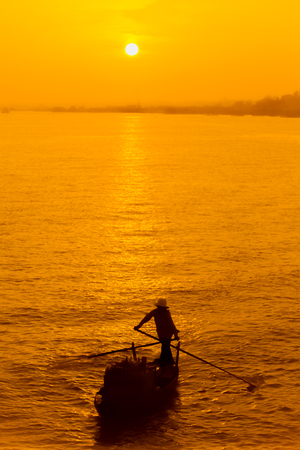 Fishing boat on Mekong river in Vietnam at sunset