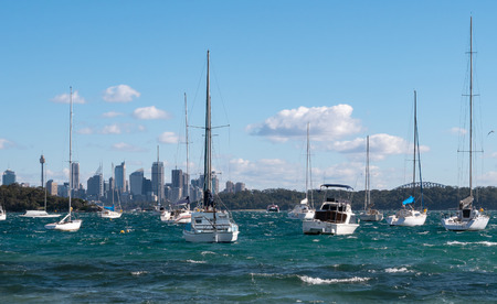 Sailing boats at anchor with Sydney skyline in the background