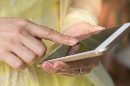 Close up of a women using mobile smart phone outdoor.