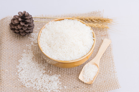 jasmine rice: Jasmine Rice in bowl with rice plant on white background. Stock Photo