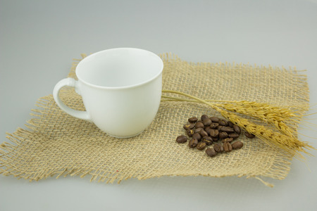 Coffeecup with coffeebeans on gunny textile isolate background. Stock Photo