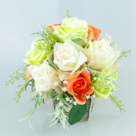 Colorful flower arrangement centerpiece in square glass vase.