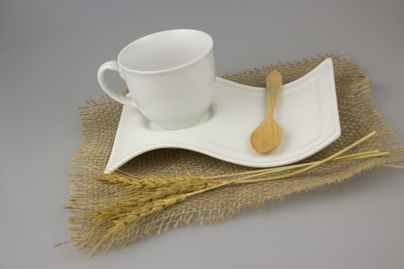 Coffee cup with teaspoon on gunny textile isolate background. Stock Photo