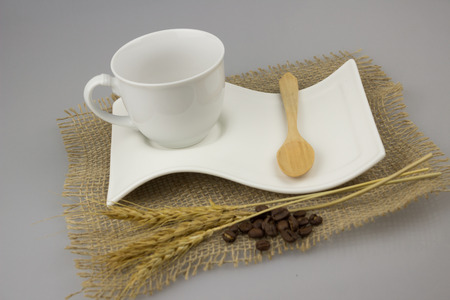 teaspoon: Coffee cup with teaspoon on gunny textile isolate background. Stock Photo