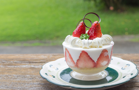 A small dessert with some strawberry with mint leaves.