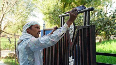 22 February 2021-Khatoo, Jaipur, India. Portrait shot of Indian painter making paint art on Enter gate. Renovation of gate with oil paint.