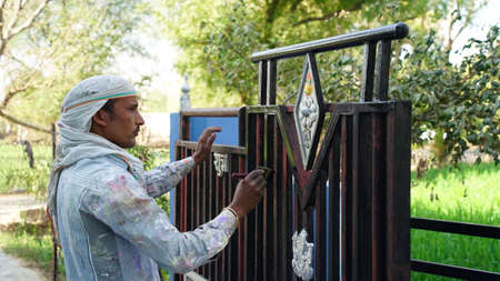 22 February 2021-Khatoo, Jaipur, India. Contractor's hand on Iron fence gate. Painter making oil paint with brush on Iron enter gate.
