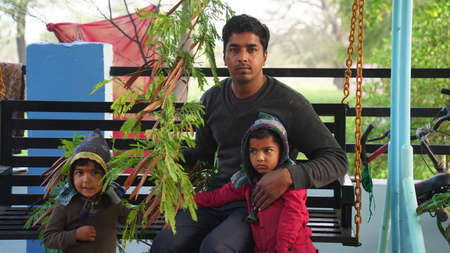 An young Indian sitting in a park with his children. Man holding Siris or Albizia Lebbeck plant branch.