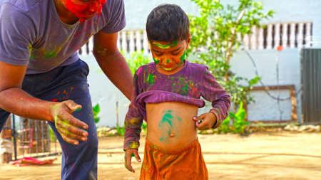 Cheerful kid playing Holi and showing uncover body with smeared color. Child enjoying Holi festival.