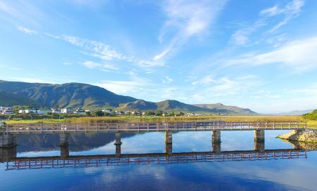 Brücke über die Lagune mit Bergen Standard-Bild - 79039438