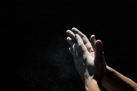 magnesia: Hands with white powder and black background