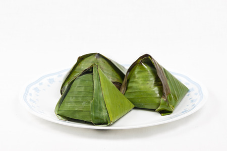 Simple and authentic nasi lemak wrapped in banana leaf served on plate photo