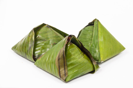 3 packs of simple and authentic nasi lemak wrapped in banana leaf. photo