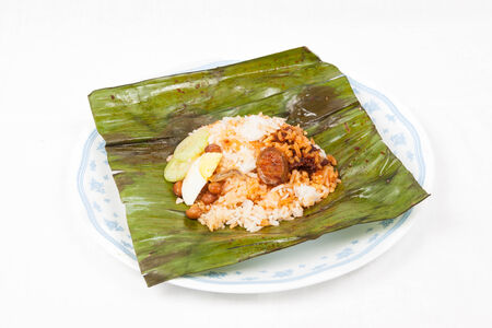 Simple and authentic nasi lemak wrapped in banana leaf served on a plate photo