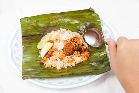 malaysia culture: Savoring the simple and authentic nasi lemak wrapped in banana leaf. Stock Photo