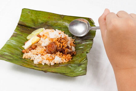 lemak: Savoring the simple and authentic nasi lemak wrapped in banana leaf. Stock Photo