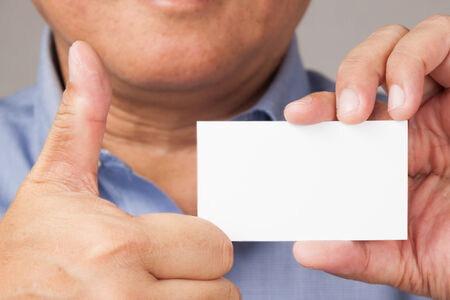 A closed up shot of a businessman holding a white blank business card with thumb\\\\ photo