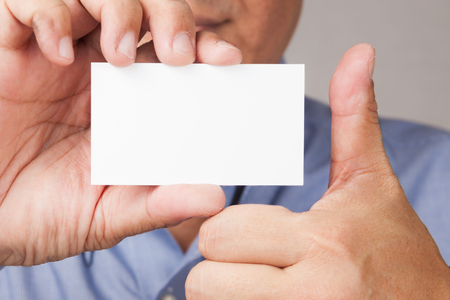 informing: A closed up shot of a businessman holding a white blank business card with thumb\\\\