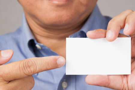 A closed up shot of a businessman holding and pointing to a white blank business card. photo