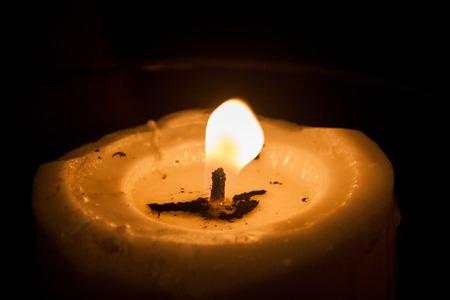 easter candle is burning: Single candle light illuminates a dark surrounding Stock Photo