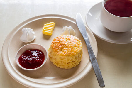 original plate: English scones set with a cup of tea served on a table next to window, illuminated with natural light Stock Photo